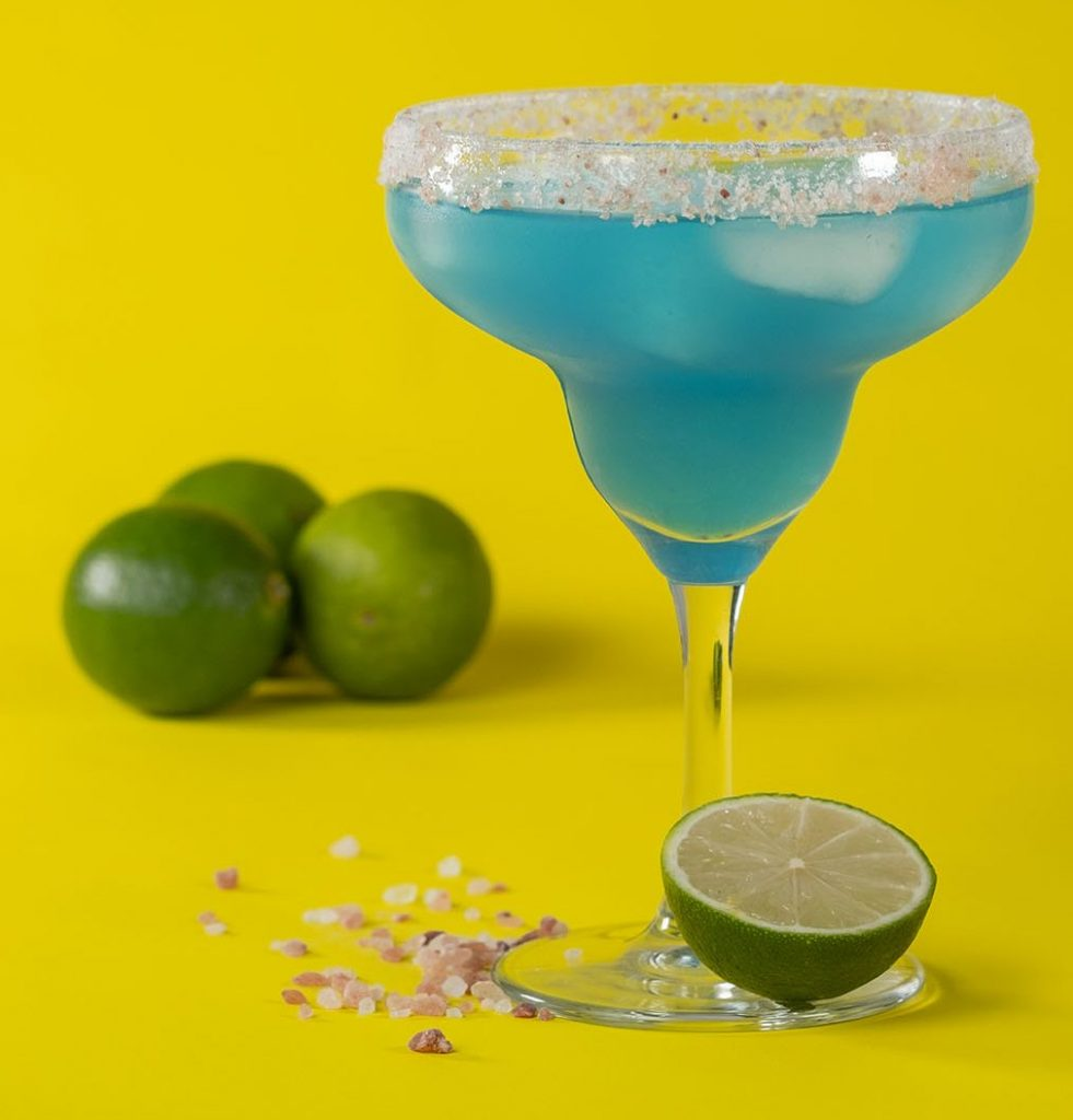 Blue margarita on yellow background with limes