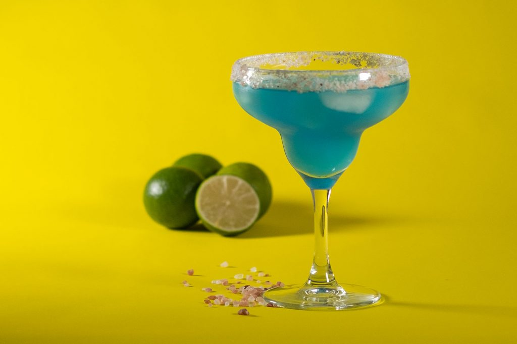 blue margarita with limes and himalayan salt on yellow background