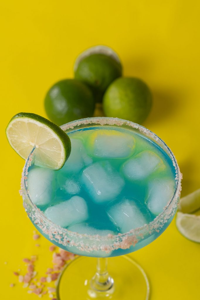 blue margarita with limes and salt garnished with a slice of lime and glass full of ice