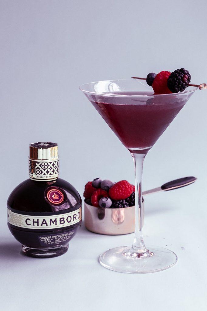 Chambord Martini garnished with berries and fresh fruits on the white background