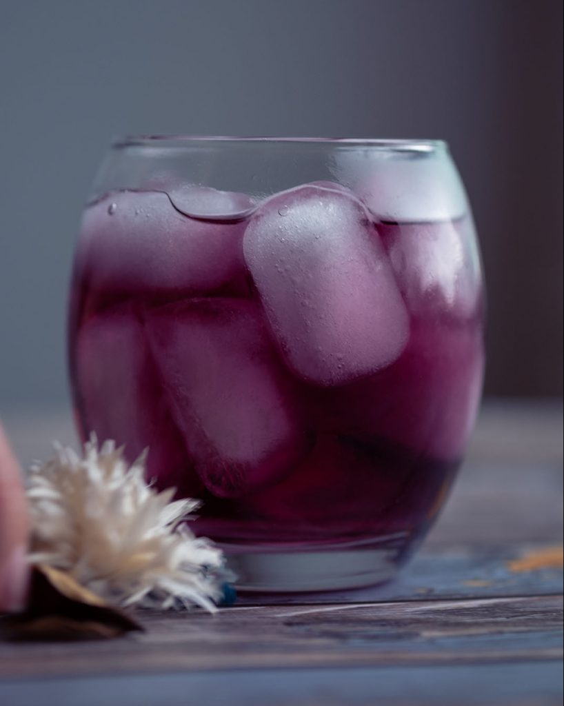 purple cocktail in a glass filled with ice