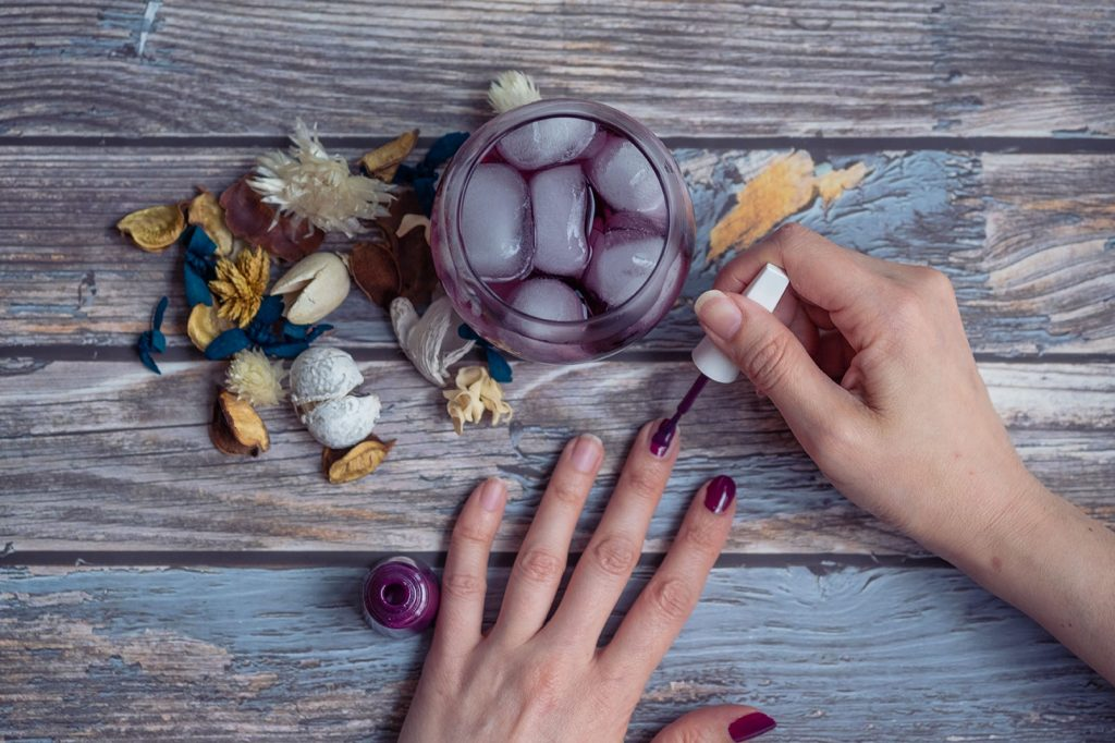 hand painting nails with purple nail polish and a purple cocktail on a wooden table with some dry flowers